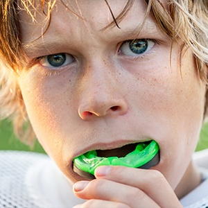 Teen placing mouthguard